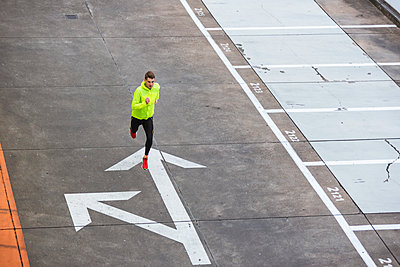 Young man running on parking level - p300m1449836 by Daniel Ingold