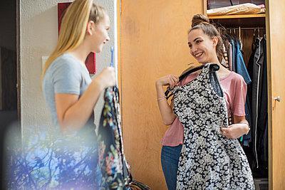 Two smiling teenage girls choosing clothes from wardrobe - p300m2005261 von zerocreatives