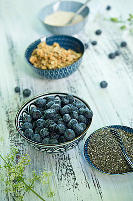Bowls of blueberries, black chia seeds, granola  and amaranth - p300m2024053 von Achim Sass