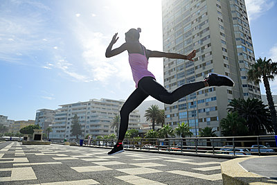 Sportive woman jumping outdoors - p300m2079318 by Eyecatcher.pro