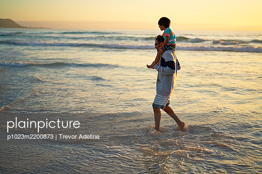 Father carrying son on shoulders in ocean surf at sunset - p1023m2200873 by Trevor Adeline
