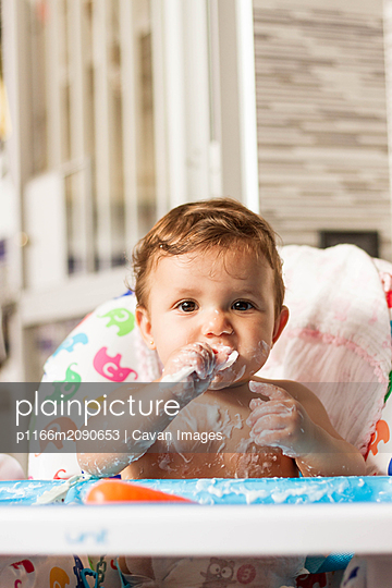 baby stained with yogurt while eating yogurt in his high chair to eat - p1166m2090653 by Cavan Images
