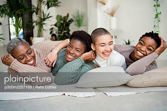 Happy female friends enjoying while lying down in living room - p300m2257169 by Rafa Cortés