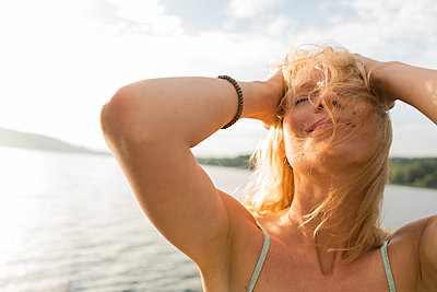 Young woman with windswept hair at a lake - p300m2140567 von Joseffson