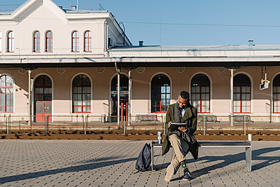 Stylish man taking notes while waiting for the train - p300m2155348 by Hernandez and Sorokina