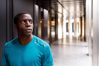 Afro man day dreaming while standing in corridor - p300m2281880 by Ignacio Ferrándiz Roig