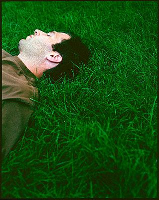 Man asleep in grass - p3720303 by James Godman