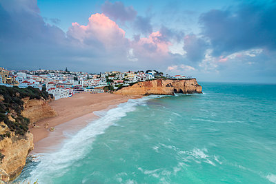 View of Carvoeiro village surrounded by sandy beach and turquoise sea at sunset, Lagoa Municipality, Algarve, Portugal, Europe - p871m1448405 by Roberto Moiola