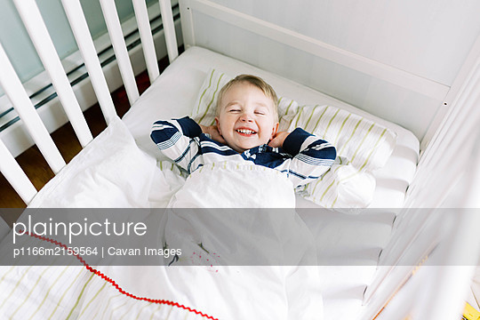 Little toddler boy in his crib not wanting to nap. - p1166m2159564 by Cavan Images