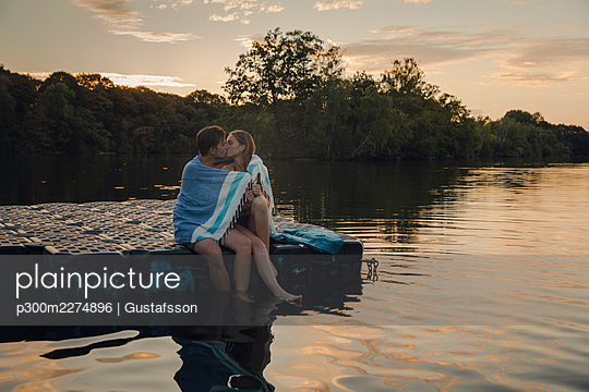Young couple sitting on bathing platform, kissing, wrapped in towel - p300m2274896 by Gustafsson