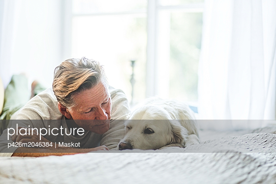 Close-up of senior man looking at cute dog while lying on bed in bedroom - p426m2046384 by Maskot