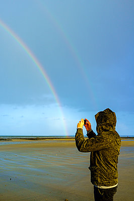 A man taking a picture of Double rainbow at the beach - p1096m1538525 by Rajkumar Singh