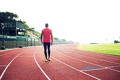 Rear view of male athlete walking on running tracks - p1166m1088132f by John Trice