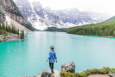 Rear view of woman in fedora hat standing on rock by Moraine Lake against mountains - p1166m1488878 by Cavan Images