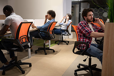 Multiethnic colleagues sitting at desks in coworking space - p1166m2234865 by Cavan Images