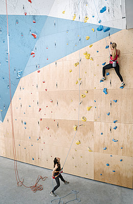 Woman with a rope securing partner on the wall in climbing gym - p300m2170522 by Hernandez and Sorokina
