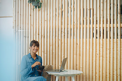 Smiling businesswoman holding coffee cup sitting by wooden wall in cafe - p300m2225880 by Gustafsson
