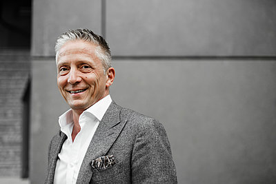 Smiling well-dressed male investor in front of gray wall - p300m2276621 by Sandro Jödicke