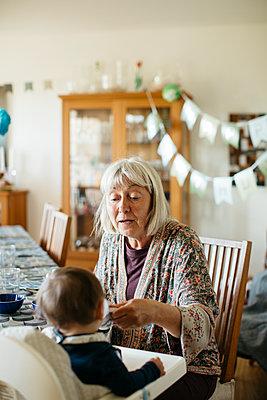 Grandmother feeding grandchild - p312m2139314 by Amanda Falkman
