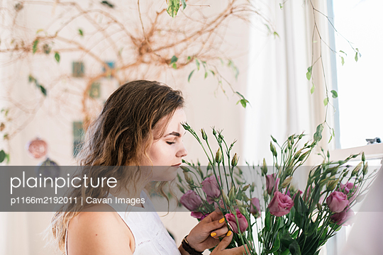 Boho teenager smelling fresh flowers isolate at home - p1166m2192011 by Cavan Images