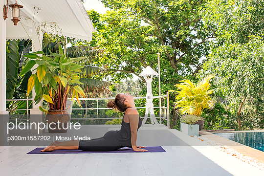 Woman practicing yoga on terrace at the poolside - p300m1587202 von Mosu Media
