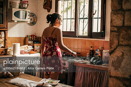 Rear view of woman cooking in kitchen - p300m2131663 by Aitor Carrera Porté