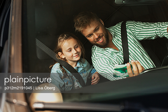 Father with daughter in car taking selfie - p312m2191045 by Lisa Öberg