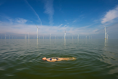 Woman in the sea in the background a wind farm - p1132m2291566 by Mischa Keijser