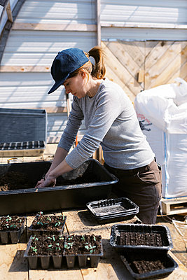 A young female farmer preparing soil blocks for her flower seeds - p1166m2269677 by Cavan Images