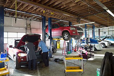 Mechanics working on engine in auto repair shop - p1192m1128069f by Hero Images