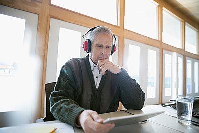 Serious senior man with headphones using digital tablet - p1192m1212930 by Hero Images
