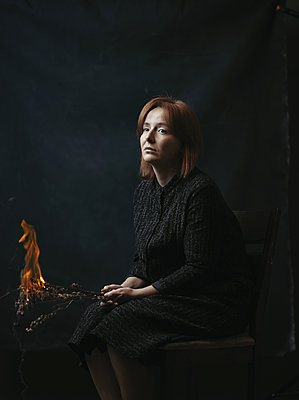 Sad woman sitting on the chair and holding burning flowers - p1577m2217417 by zhenikeyev