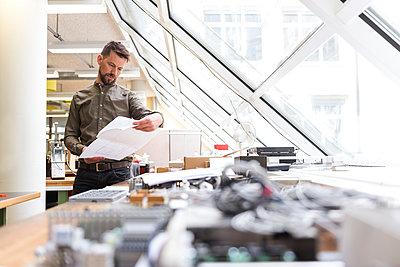 Man in factory looking at plan - p300m1586990 von Daniel Ingold