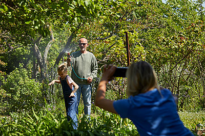 Mother taking picture of grandfather and granddaughter playing with garden hose in allotment garden - p300m2198606 by Maya Claussen