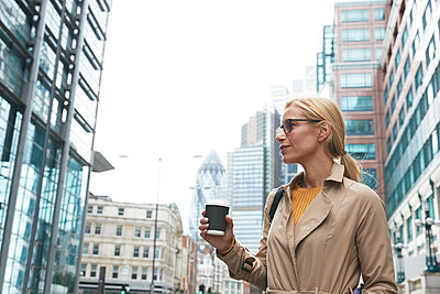 Businesswoman with coffee cup looking away while standing in city - p300m2227057 by Pete Muller
