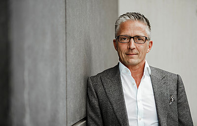 Businessman wearing eyeglasses leaning on gray wall - p300m2282812 by Sandro Jödicke