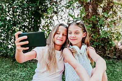 two kid girls sittingon grass and using mobile phone, summertime, Madrid, Spain - p300m2287418 von Eva Blanco