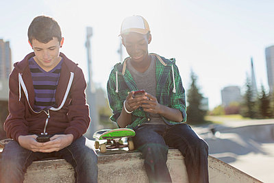 Teenage boys texting on smart phones at skate-park. - p328m784003f by Hero Images