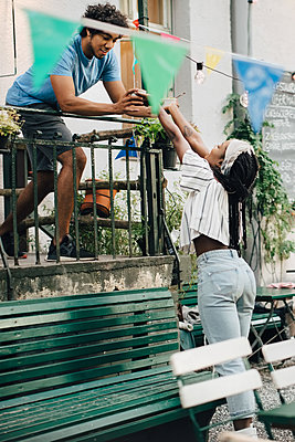 Young man giving food to female friend from balcony during garden party - p426m2046217 by Maskot