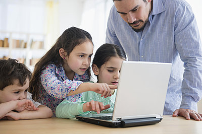 Caucasian father and children using laptop - p555m1412546 by JGI/Jamie Grill