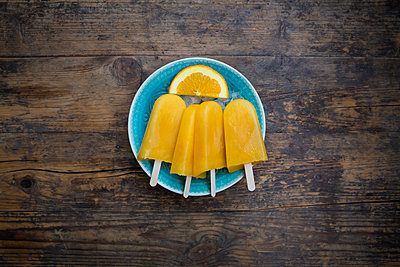 Home-made orange popsicles in bowl - p300m2005526 von Larissa Veronesi