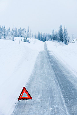 A warning triangle on a country road in the winter Sweden. - p31217863f by Jakob Fridholm