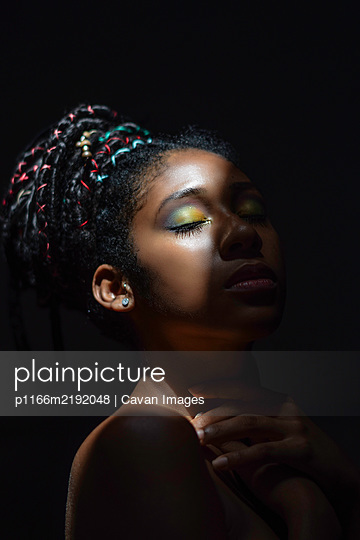 Interior chiaroscuro portrait of young black woman - p1166m2192048 by Cavan Images