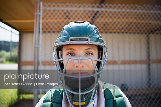Close up portrait serious middle school girl softball catcher wearing helmet