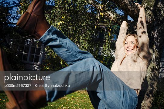 Woman having fun, climbing a tree in her garden - p300m2167337 by Kniel Synnatzschke