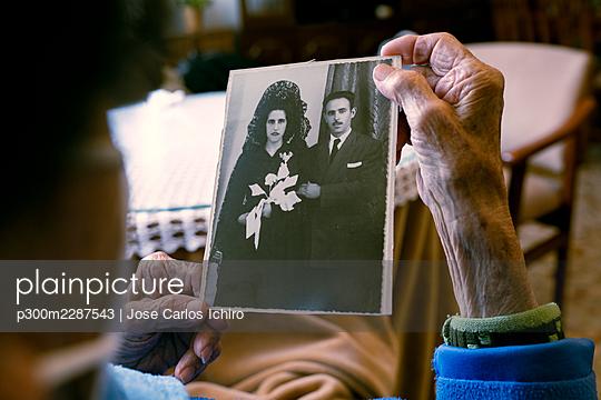 Senior woman looking at old photograph at home - p300m2287543 by Jose Carlos Ichiro