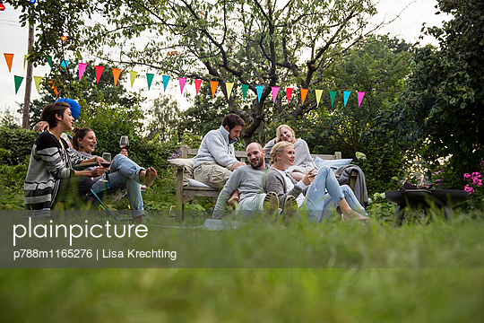 Freunde feiern eine Gartenparty - p788m1165276 von Lisa Krechting