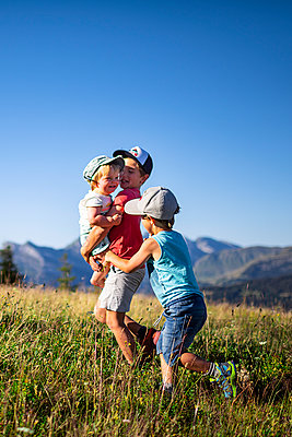 Three children playing on mountain pasture, France - p1007m2219934 by Tilby Vattard