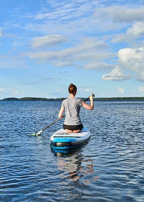 Frau sitzt auf Stand up Paddle Board - p1124m1165536 von Willing-Holtz