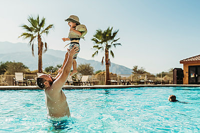 Father throwing young boy up in air while playing in pool on vacation - p1166m2218189 by Cavan Images